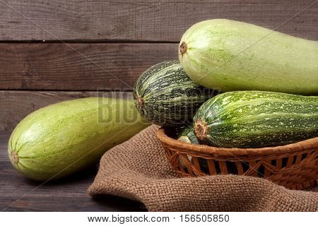 green zucchini and courgettes on sackcloth and wooden background.