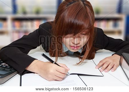 Sleepy and tired business woman at desk holding a pen for writing and close her eyes in library - business concept
