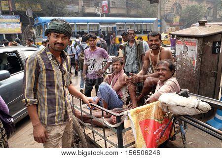 KOLKATA, INDIA - FEBRUARY 10: Indian rickshaw drivers posing sitting on tricycle rickshaw in Kolkata, India on February 10, 2016.