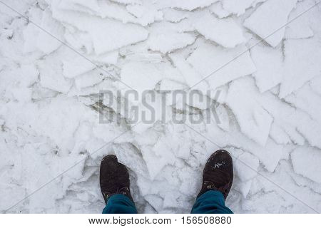 Hiking boots on river cracked ice, top view. Concept of danger of an exit to weak ice