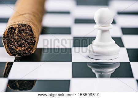 Cigar laying on the reflective surface of chess board with white pawn. Macro view. Concept of choice a sort of leisure