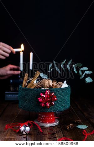 Festive Christmas Tin Filled with Nuts and Aromatic Spices and Person Lighting Candles in Background