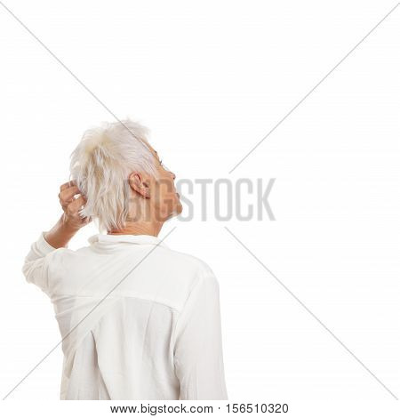 puzzled older woman scratching her head and looking up to copy space