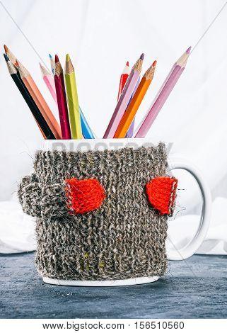Mug in wool warmer full of color pencils