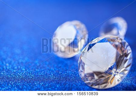 Large expensive diamonds laid on blue sparkling sequins background macro . Big brilliant closeup.