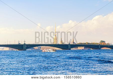ST PETERSBURG RUSSIA-OCTOBER 3 2016. Trinity Bridge and touristic pleasure boat floating under the bridge span at Neva River and Peter and Paul fortress belfry on the background in St Petersburg
