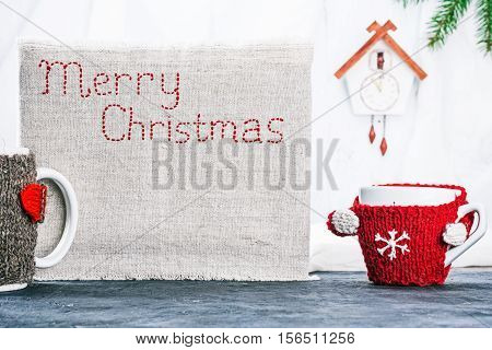 Big and little mugs in wool warmers near the canvas with stiched text 'Merry Christmas'