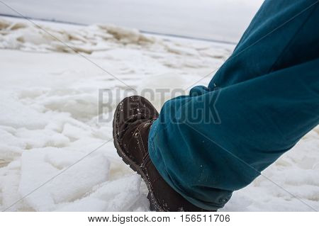 Male Feet On The Weak Bad River Ice. Concept danger falling through the ice.