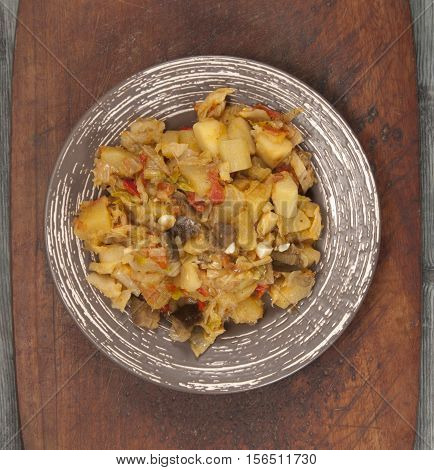 Boiled vegetables in a plate on a timber board