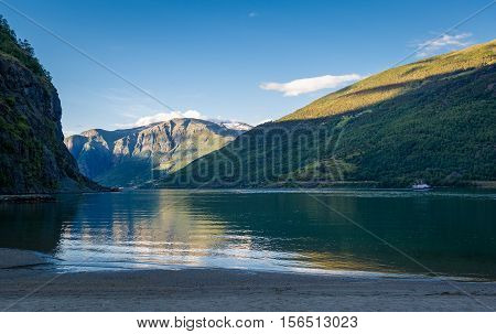 Sognefjord sand beach and mountains in Flam evening landscape. Flam, Norway.