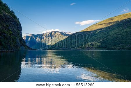 Scenic sunset view of Sognefjord mountains, with reflections on calm water. Flam, Norway.
