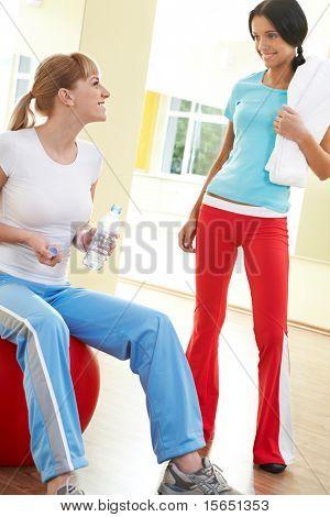 Foto von zwei Mädchen, die Kommunikation in der Turnhalle auf dem Hintergrund der Spiegel