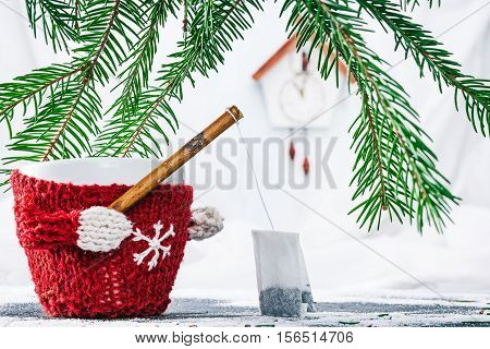 Cup in wool warmer under evergreen branches holding fishing rod with tea bag
