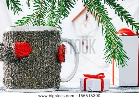 Big mug in wool warmer near the gift box under evergreen branches