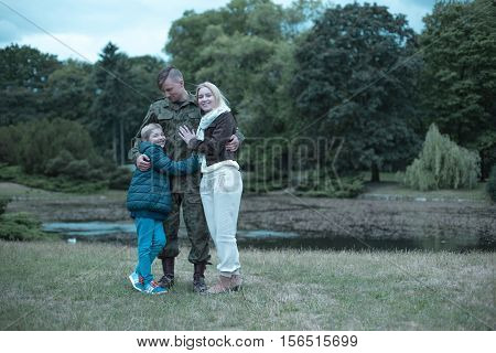 Image Of A Soldier Embracing His Wife And Son