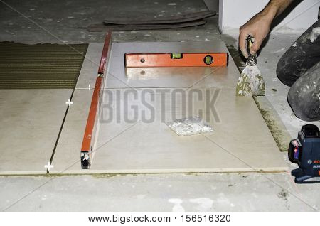 employee professionally-laying floor tiles in the kitchen