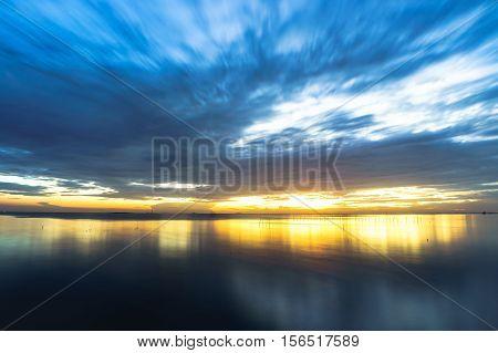 Tranquil scene cloudy sea sunset with seagulls flying at sunset at Bang Poo Recreational Retreat Samut Prakan Thailand.