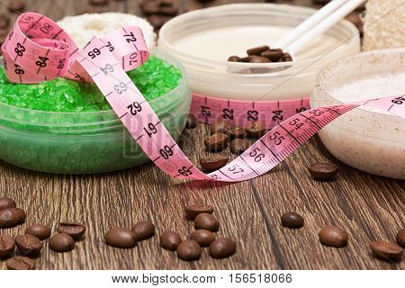 Anti-cellulite cosmetic products with caffeine. Close-up of jars filled with sea salt, natural body scrub, cellulite cream surrounded by coffee beans and body measuring tape. Shallow depth of field