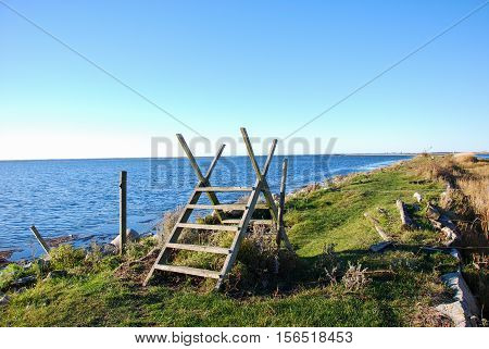 Coastal wooden stile by a footpath along the coast with calm blue water at the swedish island Oland