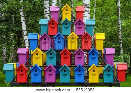Stacked rows of colorful birdhouses. New multicolored nesting boxes in vintage style.