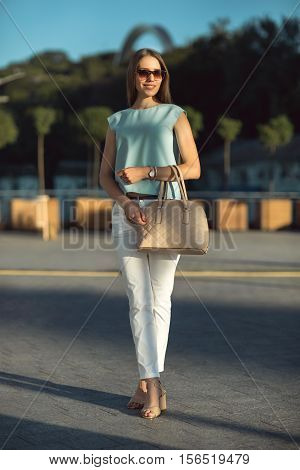 Beautiful smiling brunette young business woman wearing sunglasses, white pants, blue top and handbag, standing on the street