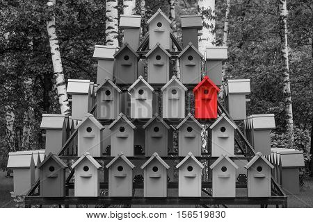 Red color wooden birdhouse stand out from the crowd. Metaphor to business concept. Stands out among the gray of similar objects. Notable among the competitors. poster