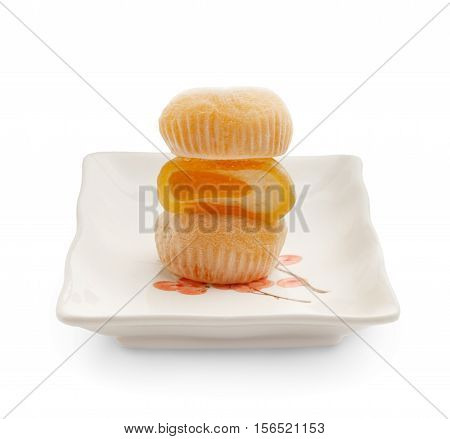 Beautiful mango mochi rice cakes in a cut standing on each other on white square ceramic plate isolated on white background.