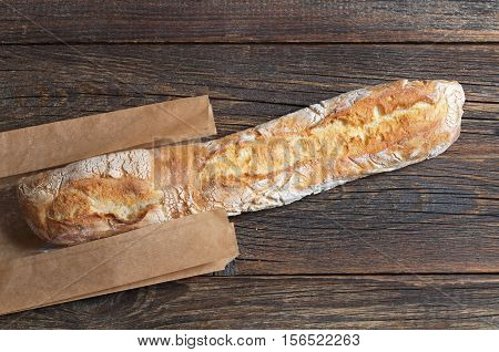 Fresh ciabatta bread on dark wooden table with paper package top view