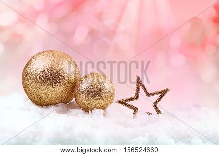 Snowball and gold star on snow field in pink blurred background with ray light effect for Christmas background.