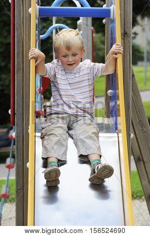 Funny toddler boy having fun on slide on playground