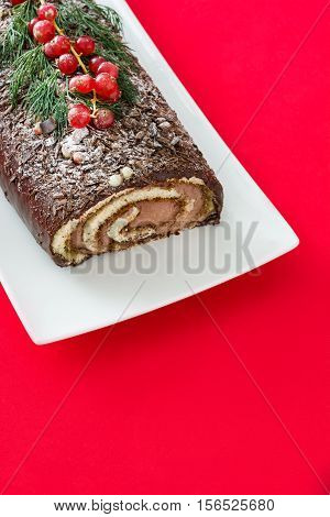 Chocolate yule log christmas cake with red currant on red background