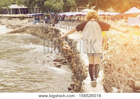 woman traveler hold ukulele guitar walking on stone path beside sea . copy space for text. concept of travel enjoy and relax life . vintage tone sunshine effect.