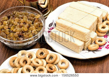 Glass cup of tea in an aluminum cup holder with fragrant green bagels wafers and raisins on tablecloth