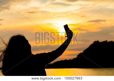 Silhouettes Of Young Women Sitting During Sunset And Take A Selfie With Smartphone. Hipster  Having