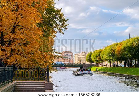 SAINT PETERSBURG RUSSIA-OCTOBER 3 2016. Water area of Moika river in sunny evening in Saint Petersburg Russia. City landscape of Saint Petersburg Russia with touristic pleasure boats on Moika river