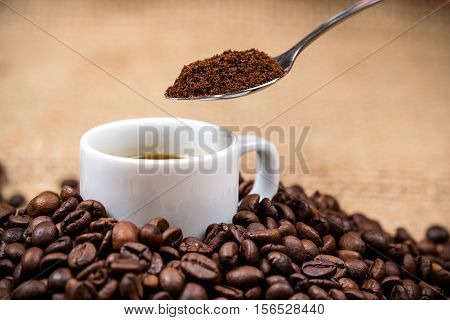 White coffeecup on coffeebeans with spoon above on gunny background