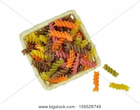 Colorful raw pasta in a basket. Top view. Ingredients. Isolation on a white background without shadows. Close-up.