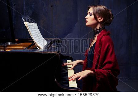 Side mid shot of charming woman in eveningwear with lace black necklace and red scarf playing solo without any accompaniment. Sitting on chair at the piano