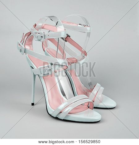 stylish light blue female stiletto shoes in grey background.
