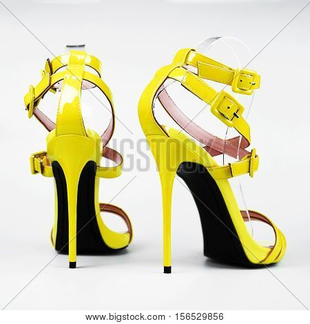 Fashionable yellow woman stiletto shoes on white background