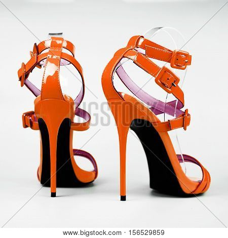Fashionable orange woman stiletto shoes on white background