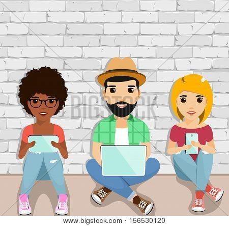 The concept of active users of gadgets. Young people sitting on the floor using gadgets. Happy people