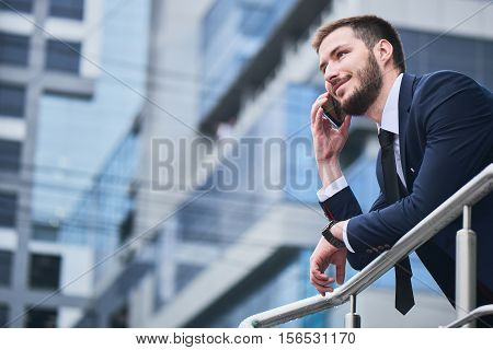 Businessman talking on cell phone against the building with a glass facade