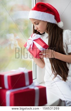 little girl in a christmas cap holding a gift sitting by the window