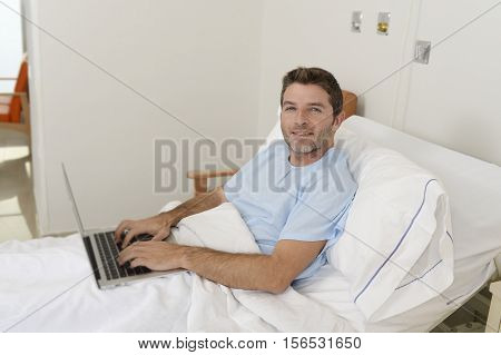 young businessman intern as patient in hospital suffering disease and working at the clinic bed with laptop computer smiling happy and relaxed in workaholic concept