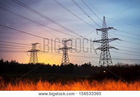 High voltage power tower and silhouette power lines sunset