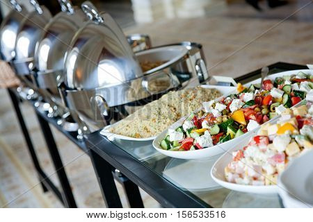 banquet glass table covered with salads on white plates