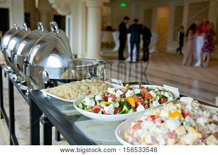 banquet table covered with salads and with people in the background
