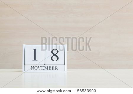 Closeup surface white wooden calendar with black 18 november word on blurred brown wood desk and wood wall textured background with copy space selective focus at the calendar