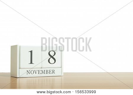 Closeup surface white wooden calendar with black 18 november word on blurred brown wood desk isolated on white background with copy space selective focus at the calendar